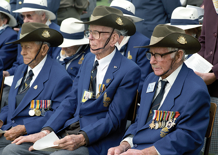 Australian veterans with their medals and slouch hats seated for a commemoration