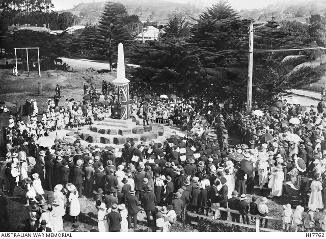 A large group of people gathered around a war memorial.