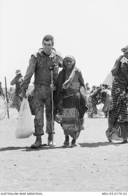 A soldier walks along side an elderly native woman in a large sandy area with other people in the background
