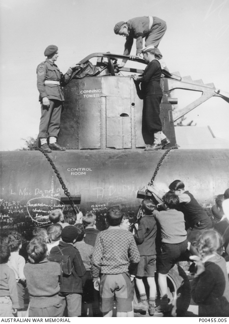 Three male soldiers standing on top of a submarine with a small crowd of boys and girls looking on.