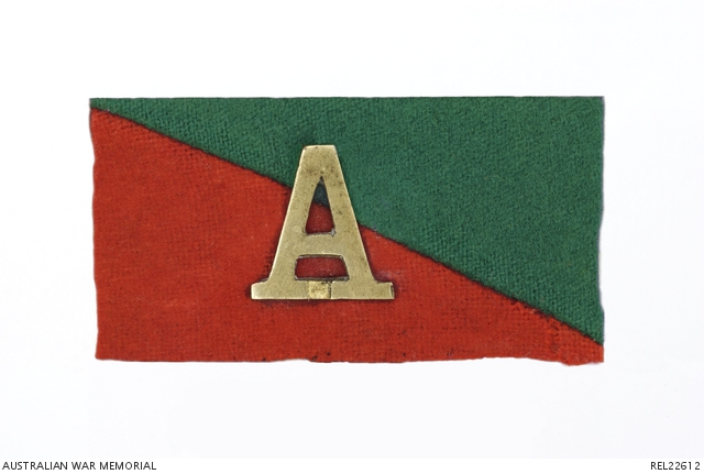 A green and red colour patch with a brass letter A in the centre