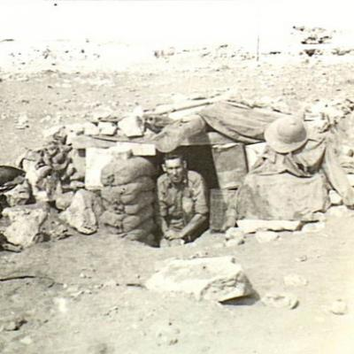 A man at the opening of a shelter dug in the ground and covered over by sandbags and rocks
