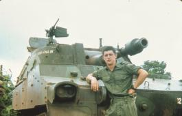 A male soldier standing in front of a tank.